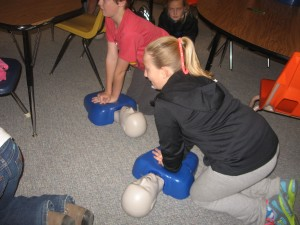 Students practicing CPR compressions for an adult.