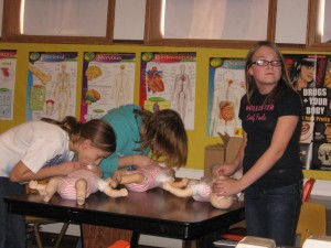 Students practicing giving CPR breaths to an infant.